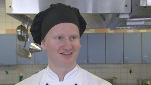 Ung kockstuderande man i kockmössa i undervisningskök.