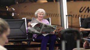 Jennifer Townsend sitter i en flygterminal och läser en tidning.