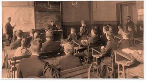 Tyttöjä ja poikia maantiedon tunnilla Brobergskan yhteiskoulussa1890-luvulla.