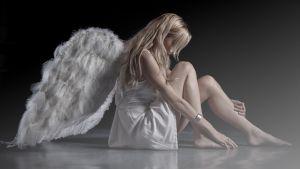 lattialla istuu tyttö jolla on siivet selässä
