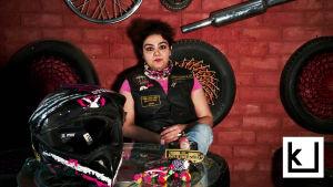 Intialainen nainen moottoripyöräaiheisten tavaroiden ympäröimänä.