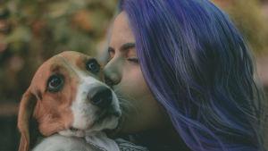 Nainen pitää koiraa sylissä ja pussaa koiraa.