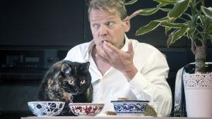 Risto Kuusisto syö kissansa kanssa saman pöydän ääressä.