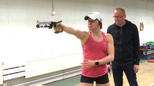 Eevi Bengs skjuter med laserpistol under Jouko Pakarinens övervakning.