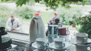 Bersåmiljö: Kaffekoppar och kaffekanna i förgrunden, personer som dricker kaffe i bakgrunden.