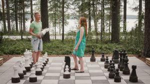Egenlandin juontajat Nicke Alden ja Hannamari Hoikkala pelaavat jättinappuloilla shakkia Sumiaisten leirintäalueella.