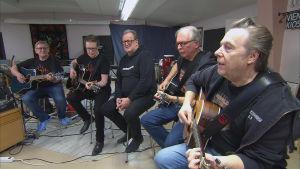 Fem mogna män sjunger och spelar gitarr