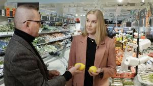 Suvi Kuutti (Lidlin laadunvalvontapäällikkö) ja toimittaja Matti Toivonen sitruunat kädessä Graniittitalon Lidlin hedelmäosastolla.