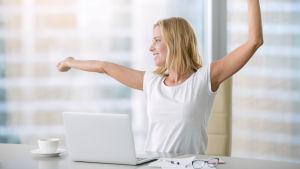 Nainen venyttelee selkää tietokoneen äärellä.