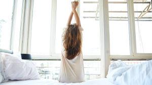Nainen venyttelee selkäänsä juuri herättyään.