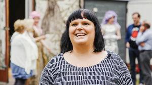 Mari Paloniemi taustallaan sumeana La Kala -oopperatalon väkeä esiintymisasuissa, taustalla oopperatalo eli autotalli