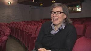 Författaren Lena Andersson sitter i en teatersalong och skrattar.
