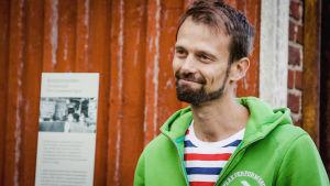 Vanhan Malmin asukas Anders Jungar kuvattuna punaisen puutalon edustalla, päällä vihreä huppari, raidallinen t-paita