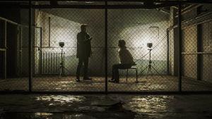Kuvassa kohtaus Karppi-tv-sarjasta: pimeässä kellarissa penkillä istuu nainen, joka on panttivankina ja hänen suunsa ja kätensä on sidottu. Hänen sieppaajansa seisoo vieressä.