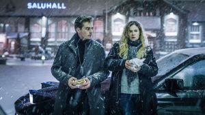 Kuvassa kohtaus Karppi-tv-sarjasta, jossa päähenkilöt seisovat ulkona lumisateessa, syövät hampurilaisia nojaillen autoonsa.
