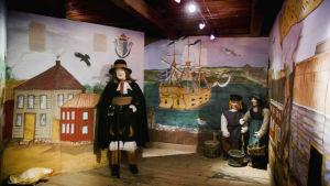 Seinän peittäviä piirroksia 1600-luvun Kristiinankaupungista, vanhoja rakennuksia, takaseinällä purjelaiva merellä, suurikokoisia nukkeja vanhoissa asuissa.