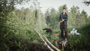 Nuori mies keskittyy kalastamiseen, pitelee onkivapaa vehreällä joenrannalla.