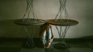 Nainen istuu pöytien alla sikiöasennossa.