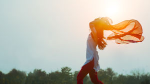 Nainen pitelee sifonkihuivia aurinkoa vasten.