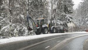 Traktori puhdistaa jalankulkuväylää lumesta