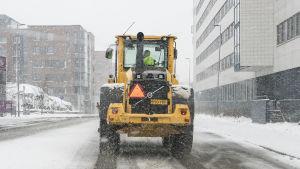 Lumiauaraustraktori ajaa tiellä lumisateessa