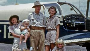 Perhe seisoo pienen lentokoneen edessä.