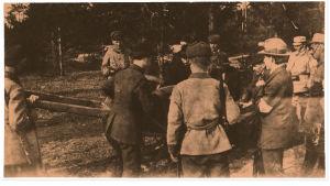 Valkoiset hautaavat Algot Untolan punaisten joukkohautaan Helsingin Santahaminan vankileirille 21.5 1918.