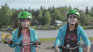 Kaksi vihreisiin pyöräilykypäriin sonnustautunutta tyttöä pyörineen.
