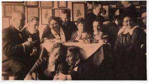 Kahvihetki Merikantojen kotona huhtikuussa. Aarre istuu lattialla edessä, isä Oskar Merikanto vasemmalla.