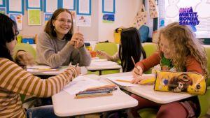 KOlme tyttöä ja Ronja Salmi istuvat luokkahuoneessa pöydän äärellä.