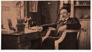 Toivo Kuula istuu työpöytänsä äärellä 1914.