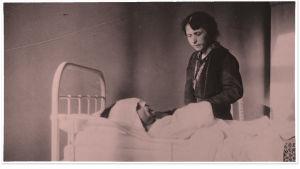 Alma Kuula seisoo Toivo Kuulan sairasvuoteen äärellä Viipurin lääninsairaalassa 1918.