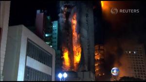 Brinnande våningshus rasar ihop.