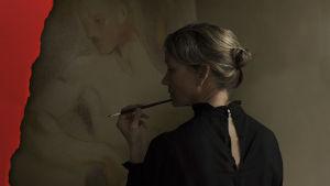 Helene Schjerfbeckiä esittävä nainen selkä kameraan päin mustassa asussaan pidellen sivellintä leuallaan. Edessä maalattu taulu.