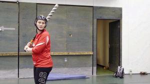 Nainen pesäpallomailan kanssa harjoittelemassa.