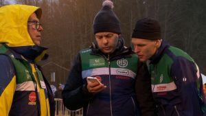Tränarna Pekka Väisänen och Henrik Tala samt orienteraren Topi Raitanen kollar mellantider under Tiomilakavlen 2018.