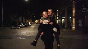 Pojkvännen bär Flickvännen på sina axlar på övergicen storstadsgata på natten.