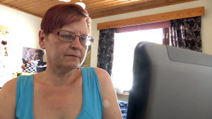 Anitta Piiroinen istuu tietokoneen äärellä.