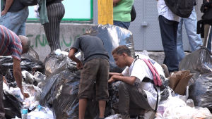 Människor letar efter mat bland soporna i Venezuela.