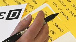 Käsi pitää kynää kädessään, taustalla post it-lappuja.