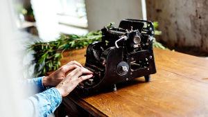 Kirjoittaja vanhanaikaisen kirjoituskoneen ääressä.
