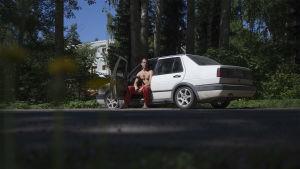 En man sitter i förarsätet av en vit bil. Bilen är gammal. Förardörren är öppen.