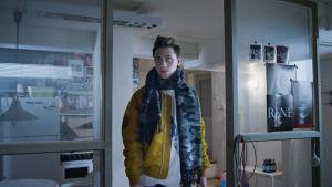 Nuori mies seisoo keskellä huonetta yksin ja katsoo vasempaan yläviistoon.