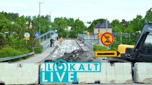 En bro där rivningsarbetet har börjat, ytlagret har skrapats bort. En cyklist och en fotgängare syns på bron. I mitten en hög asfaltrester, till höger en grävmaskin. Trafikmärke förbjuder motorfordonstrafik. Sommar, gröna träd, blå himmel.