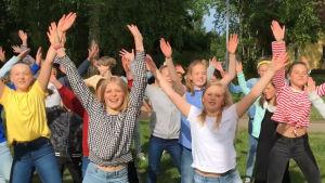 Barn dansar i grupp och sträcker händerna i luften.