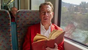 Mies istuu junassa, vanha kirja auki ja katsoo kameraan.