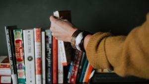 Käsi tavoittelee kirjaa hyllystä