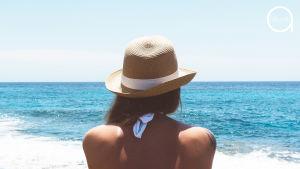 Nainen katselee merelle olkihattu päässään.