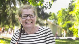 Anneli Bäckström från axlarna uppåt, sitter på en gräsmatta i lekparken Intia i Forsby i Helsingfors.