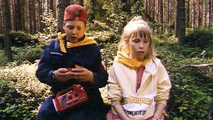 En flicka och en pojke i skogen.
